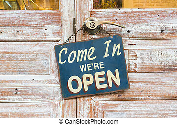 Come In We're Open on the wooden door. center of the photo....