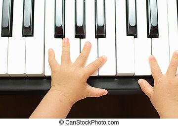 Hands of Japanese girl playing a piano (1 year old)