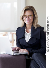 Businesswoman teleworking at home. On a Laptop. Smiling -...