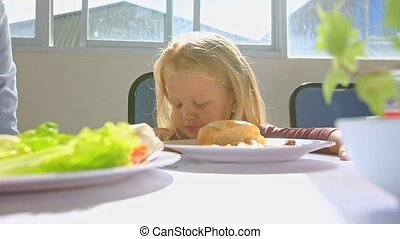 Little Blond Girl Talks at Breakfast Moves Aside Plate on Table