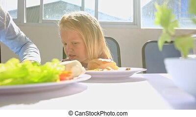 Little Blond Girl Plays with Spoon by Chicken Plate at Table