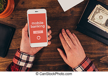 Woman using mobile banking app on smart phone in the office,...