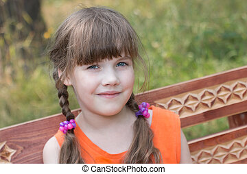 Happy pretty little girl sits on wooden beanch at sunny...