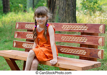 Happy cute little girl in orange sits on wooden beanch at...