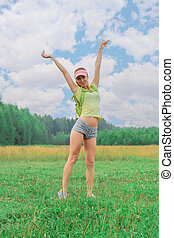 Teen girl with backpack standing outdoors with arms raised up towards the sky with your hands