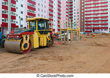 Big roller at construction site next to new building and...
