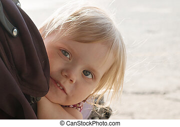 Little smiling blonde girl looks out pram outdoor, closeup,...