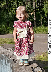 Little pretty blonde girl in dress stands in park at sunny...