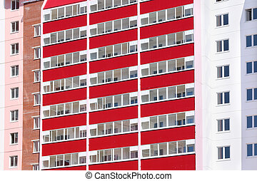 Part of new pink residential building with red balconies  at sunny day