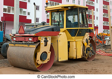 Large roller at construction site next to new building at...