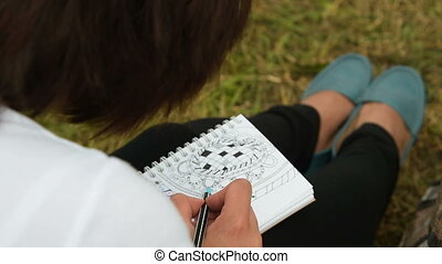 Woman spending leisure time with drawing - Young woman...