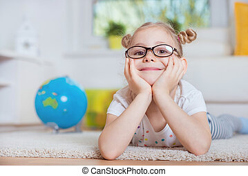 Portrait of pretty little girl on carpet at home with globe...