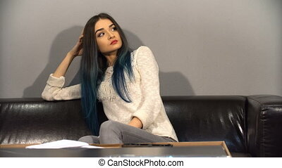 Young cute girl with colored hair sitting on a couch in their new apartment to put together a table. Shoot in kitchen.