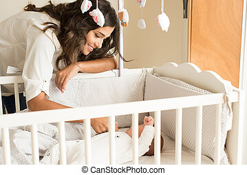 Mother putting baby to sleep at the crib