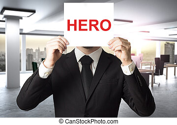 businessman in large office hiding face behind sign hero -...