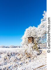 Wooden brown hunting hideout next to frozen trees - Vertical...