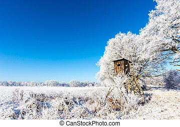 Wooden brown hunting shelter next to frozen trees -...