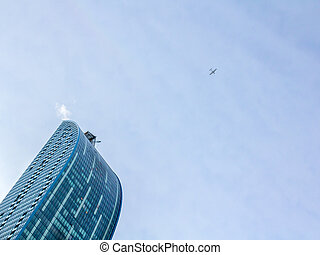 Plane flying over a skyscraper in downtown Toronto, Ontario,...