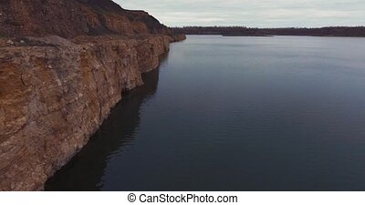 Flight to drone sand quarry. The sheer side of the lake. -...