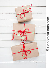 Christmas style rustic brown paper package tied up with strings. White wood background.