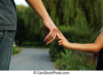 parent holds the hand of a small child - the parent holds...