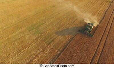 View of combine from air. Green harvester on the field....