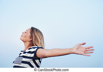 Young woman feeling free under a blue sky - Attractive young...