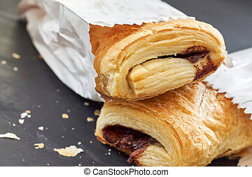 Puff pastry with chocolate filling in white paper bag on...