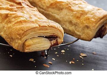 Puff pastry with chocolate filling on black wooden...