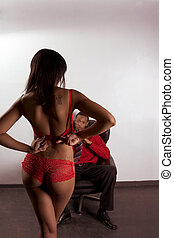 Striper woman in red dancing for young black man -...
