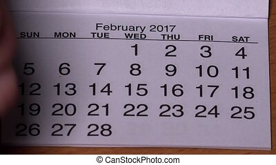female hand with red marker draw a heart shape in calendar february 14th