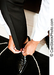 Man tying his shoes and preparing to go out for a date