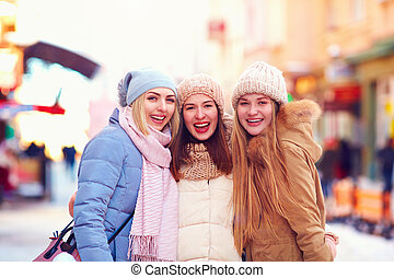 portrait of three happy girls, friends together on winter street