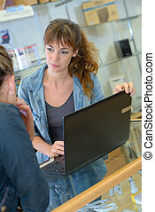 Sales assistant with laptop talking to customer