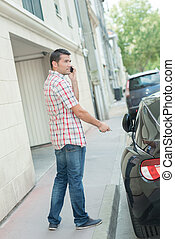 man in street next to sports car