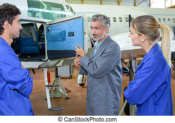 Students looking in compartment of aircraft