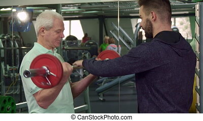 Senior man trains his bicepses - Gray senior man training...