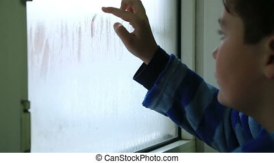 Sad child drawing sad face on the window - The sad boy the...