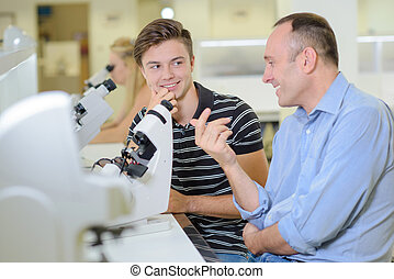 Two men chatting next to a microscope