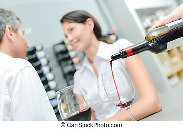 Wine being poured for couple sat together