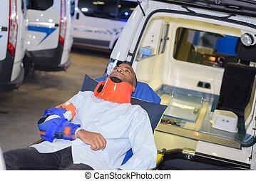 Man in neck brace beside ambulance
