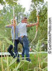 Man and woman back to back using bow and arrows