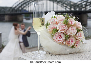 dancing wedding couple - focus on glasses and bouquet in...