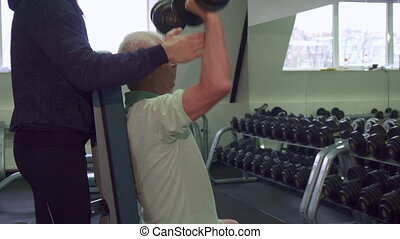 Senior man trains his shoulders - Caucasian senior man...