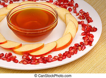 Honey, apples and pomegranate seeds - A bowl of honey, apple...