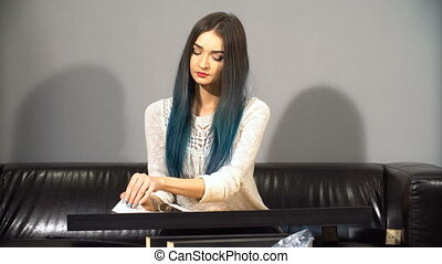Young cute girl with colored hair sitting on a couch in...