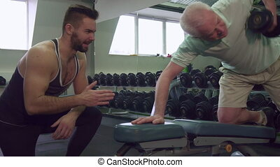 Trainer watching how senior client does exercises - Young...