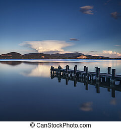 Wooden pier or jetty on a blue lake sunset and sky...