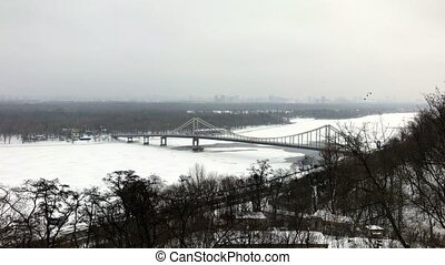 View of Parkovyi Bridge over frozen Dnipro with birds