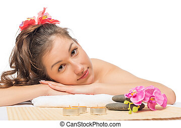 beautiful serene brunette on massage table at spa cabinet